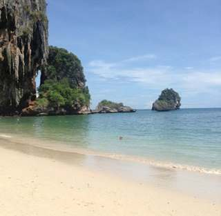 White sandy beach in Thailand bordered by cliffs