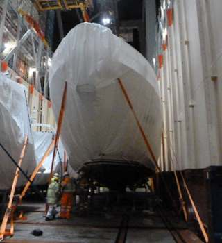 Shrink wrapped Yachts being secured to the Vessel deck