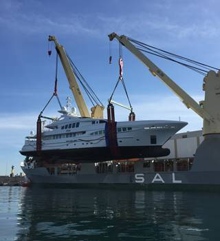 Peters & May lifting a Superyacht out of the water ready to load upon a vessel