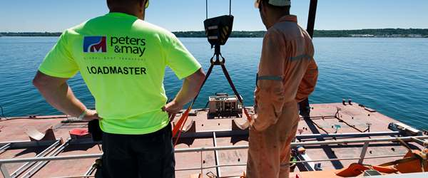 Peters & May Loadmaster directing vessel lift alongside vessel crew member
