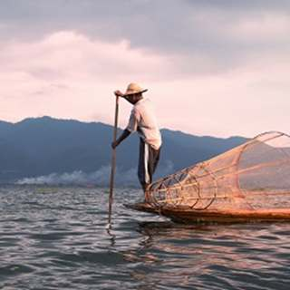 Local fisherman in traditional boat in Myanmar